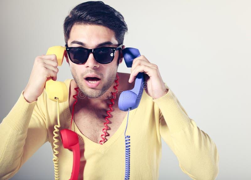 Grappige call centrekerel met kleurrijke telefoons royalty-vrije stock afbeeldingen