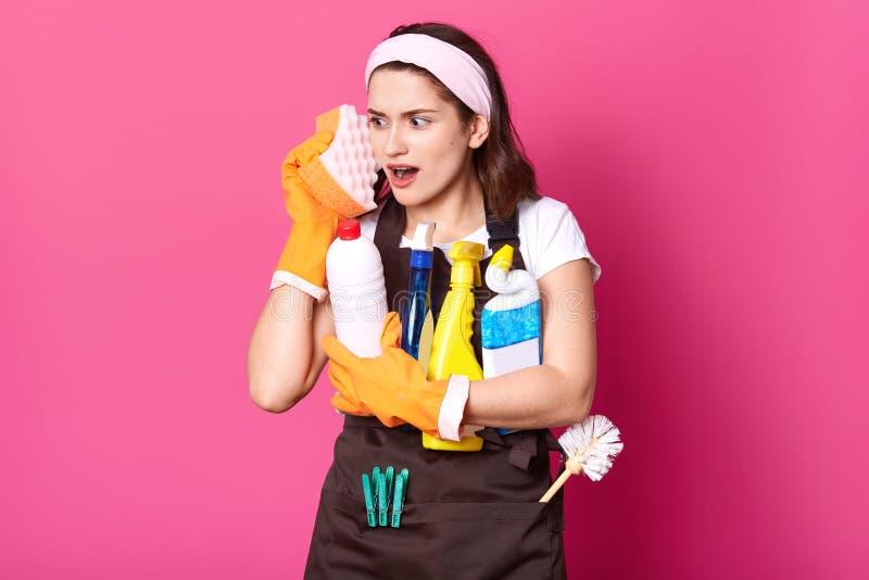 Grappige charmante jonge Kaukasische huisvrouw die toevallige t-shirt en schort, oranje rubberhandschoenen dragen, die sponsen ho stock foto