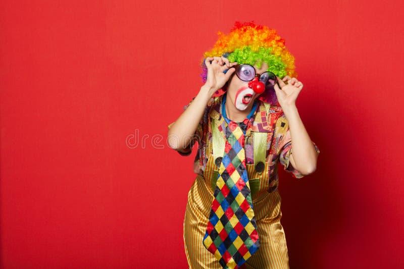 Grappige clown met glazen op rood stock afbeelding