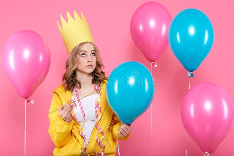 Grappige conceptuele fotografie Brutaal meisje in de holdingsnaald die van de verjaardagshoed verjaardagsballons beweren te knall royalty-vrije stock afbeelding