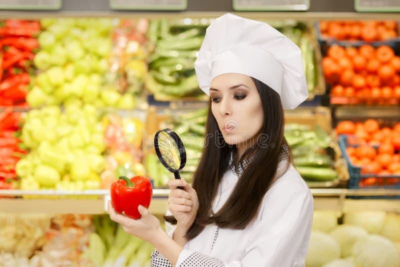 Grappige Dame Chef Inspecting Vegetables met Vergrootglas royalty-vrije stock fotografie