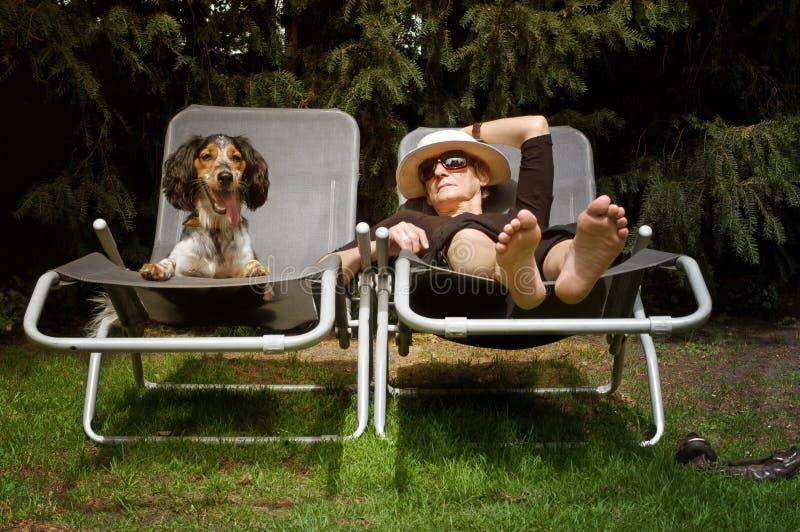 Grappige dame die met haar hond zonnebaadt royalty-vrije stock foto's