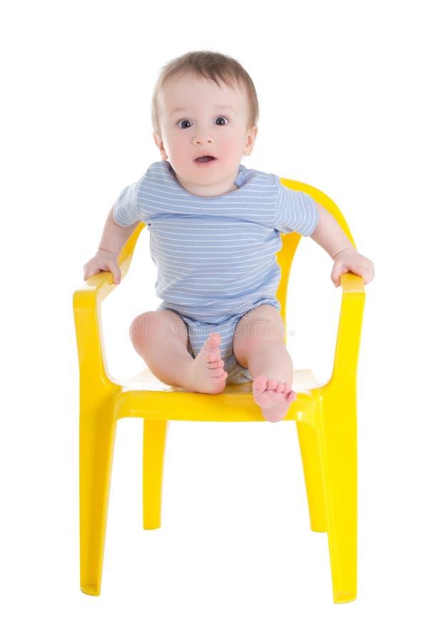 Grappige de peuterzitting van de babyjongen op weinig die stoel op wit wordt geïsoleerd royalty-vrije stock fotografie