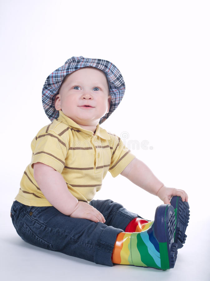 Grappige die jongen in gumboots op wit wordt geïsoleerd stock foto's