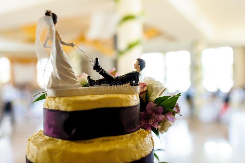 Grappige docoration van de huwelijkscake, gebonden bruidegom op de leiband van de bruid. stock fotografie