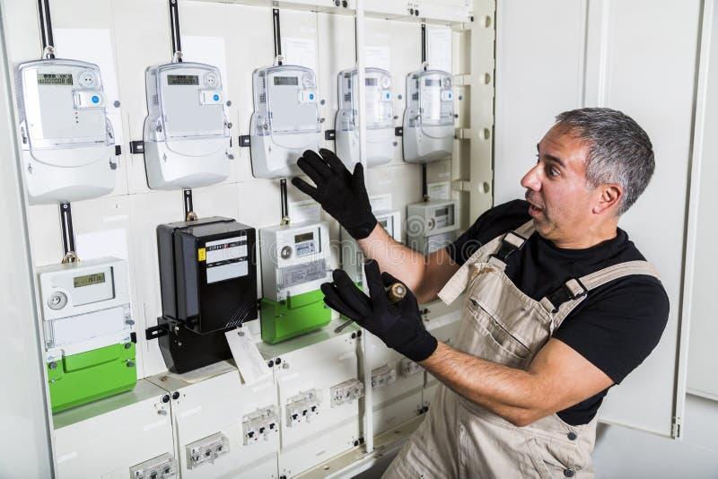 Grappige elektricien die elektroreparatie in schakelbord doen royalty-vrije stock afbeeldingen