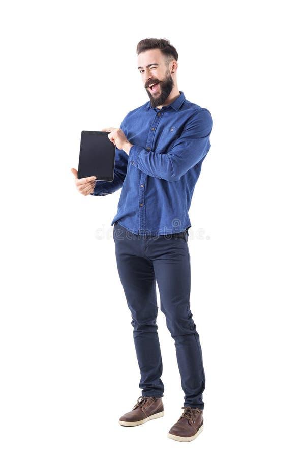 Grappige expressieve jonge gebaarde mens die het lege tabletscherm voorstellen die naar camera knipogen royalty-vrije stock afbeeldingen