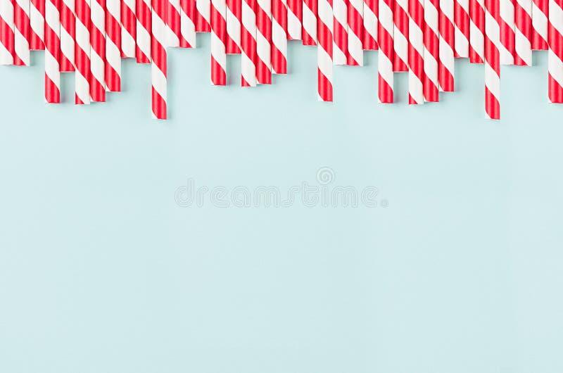Grappige feestelijke heldere abstracte achtergrond - het gestreepte rode cocktailstro op de munt van het pastelkleursuikergoed kl stock fotografie