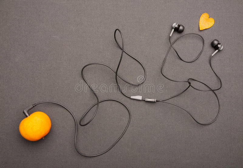 Grappige fruitige muziekspeler: hoofdtelefoons die uit van mandarin op een zwarte achtergrond komen royalty-vrije stock foto