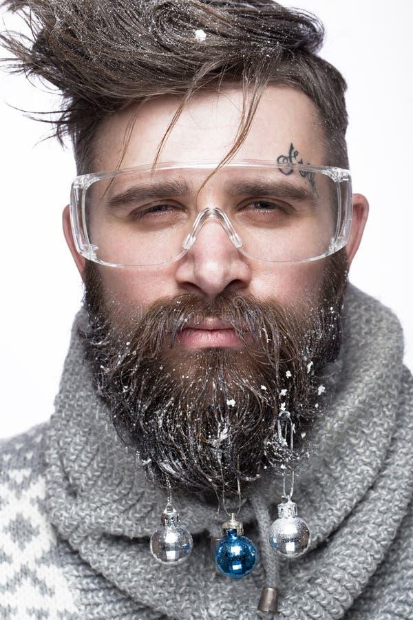 Grappige gebaarde mens in een Nieuwjaar` s beeld met sneeuw en decoratie op zijn baard Feest van Kerstmis royalty-vrije stock afbeelding