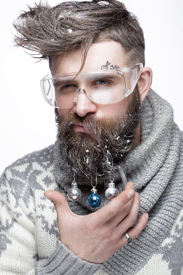 Grappige gebaarde mens in een Nieuwjaar` s beeld met sneeuw en decoratie op zijn baard Feest van Kerstmis stock afbeelding