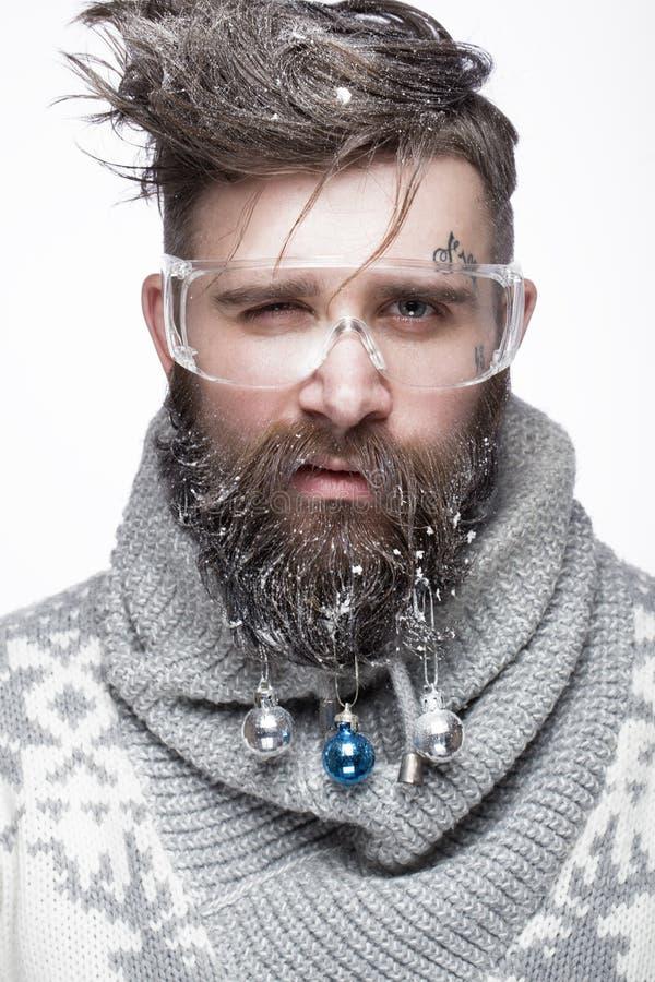 Grappige gebaarde mens in een Nieuwjaar` s beeld met sneeuw en decoratie op zijn baard Feest van Kerstmis stock foto