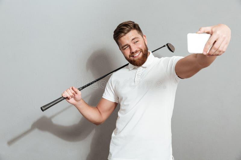 Grappige gelukkige golfspeler die selfie op zijn smartphone maken royalty-vrije stock foto