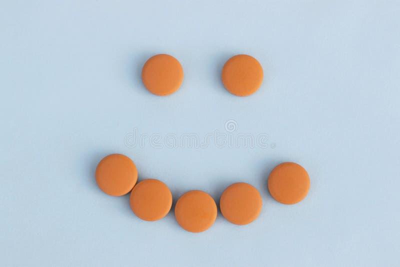 Grappige gezichten van oranje pillen op een blauwe achtergrond Concept kalmeringsmiddelen royalty-vrije stock foto