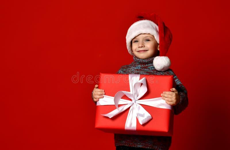 Grappige glimlachende blije kindjongen in gift van de holdingskerstmis van de Kerstman de rode hoed huidig in handen stock afbeelding