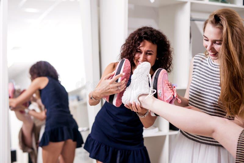 Grappige glimlachende meisjes die pret in boutique hebben die nieuw schoeisel aanbieden aan hun vriend die haar been opheffen om  royalty-vrije stock fotografie