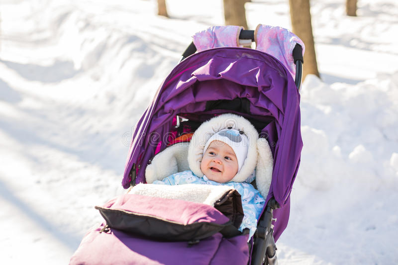 Grappige het lachen babyzitting in een wandelwagen op oude de winterdag van c royalty-vrije stock afbeeldingen