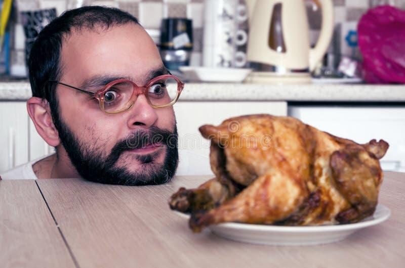 Grappige hongerige mens die op kip kijken stock afbeeldingen