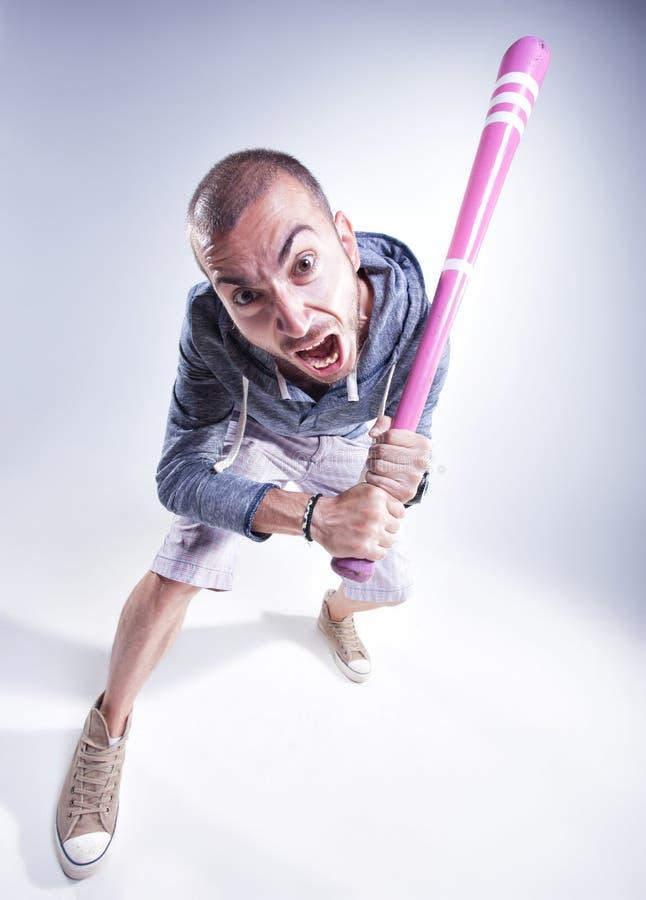 Grappige hooligan met een roze honkbalknuppel die in de studio gillen royalty-vrije stock fotografie