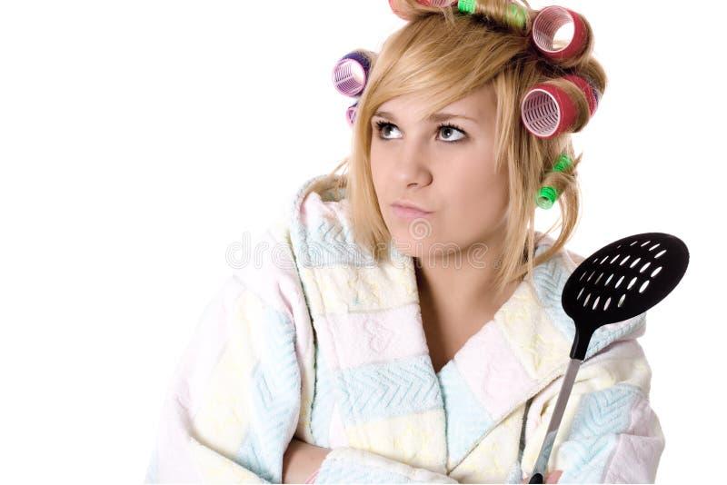 Grappige huisvrouw met krulspelden en schuimspaan stock afbeelding
