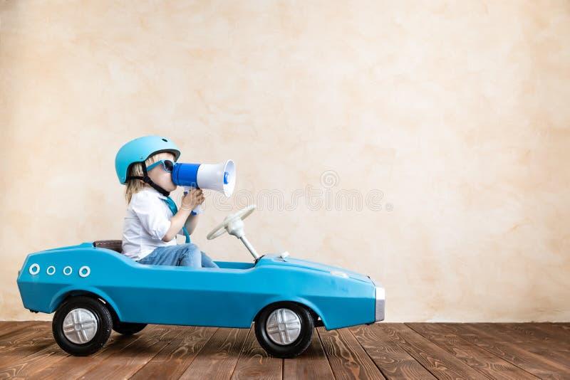Grappige jong geitje drijfstuk speelgoed auto thuis royalty-vrije stock fotografie