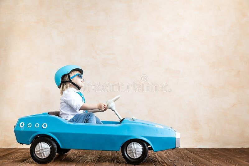 Grappige jong geitje drijfstuk speelgoed auto thuis royalty-vrije stock foto
