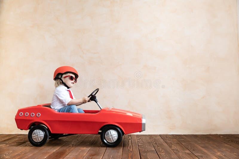 Grappige jong geitje drijfstuk speelgoed auto thuis royalty-vrije stock afbeeldingen