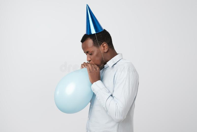 Grappige jonge Afrikaanse kerel die de ballon opblazen die blauwe partijhoed dragen royalty-vrije stock afbeelding
