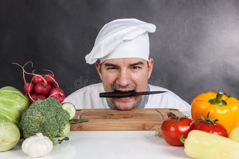 Grappige jonge chef-kok met mes en groente stock foto