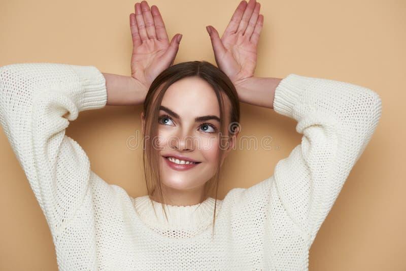 Grappige jonge dame die konijntjesoren met haar handen en het glimlachen maken royalty-vrije stock fotografie
