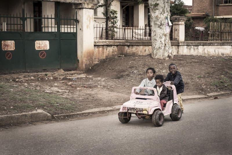 Grappige jonge geitjes die met een roestige stuk speelgoed auto in een slechte straat in Madagascar spelen royalty-vrije stock afbeeldingen