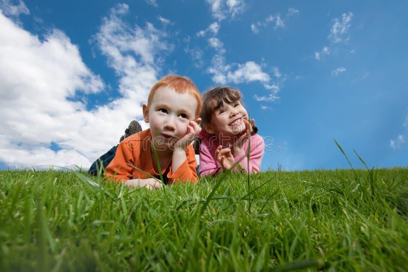 Grappige jonge geitjes die op gras met blauwe hemel liggen stock foto