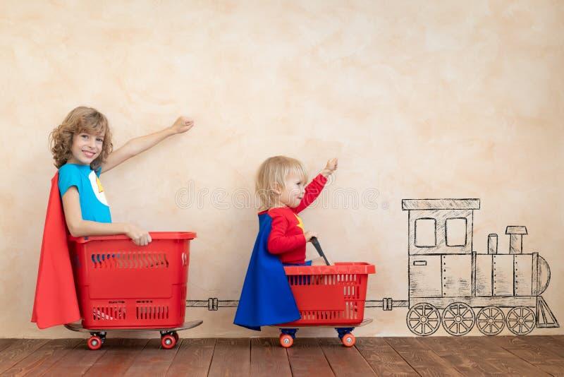 Grappige jonge geitjes die stuk speelgoed auto drijven binnen royalty-vrije stock fotografie