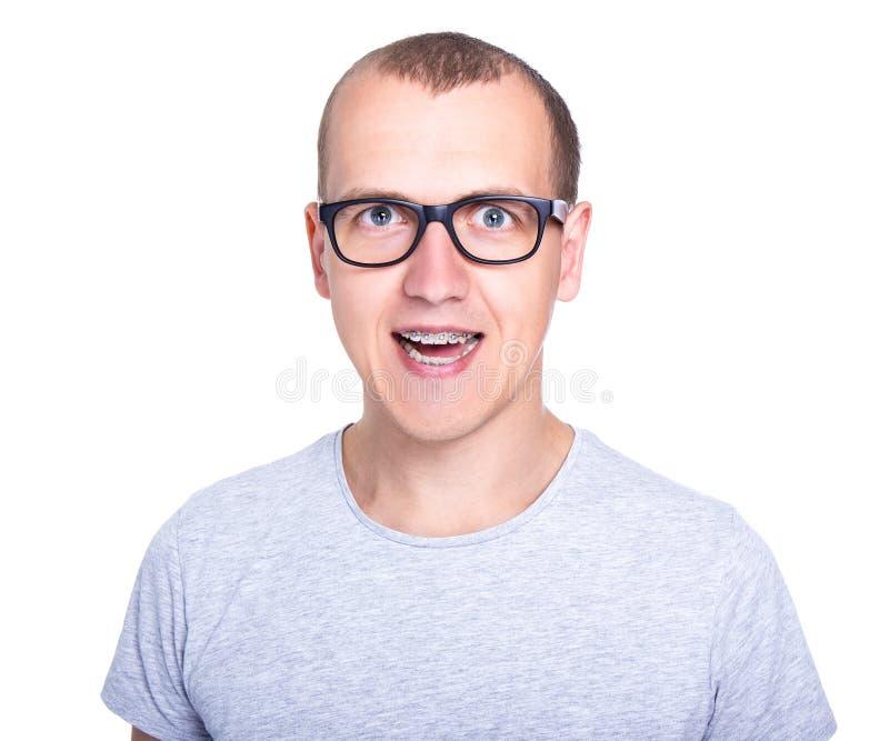 Grappige jonge mens in glazen met steunen op tanden die op whit wordt geïsoleerd royalty-vrije stock fotografie