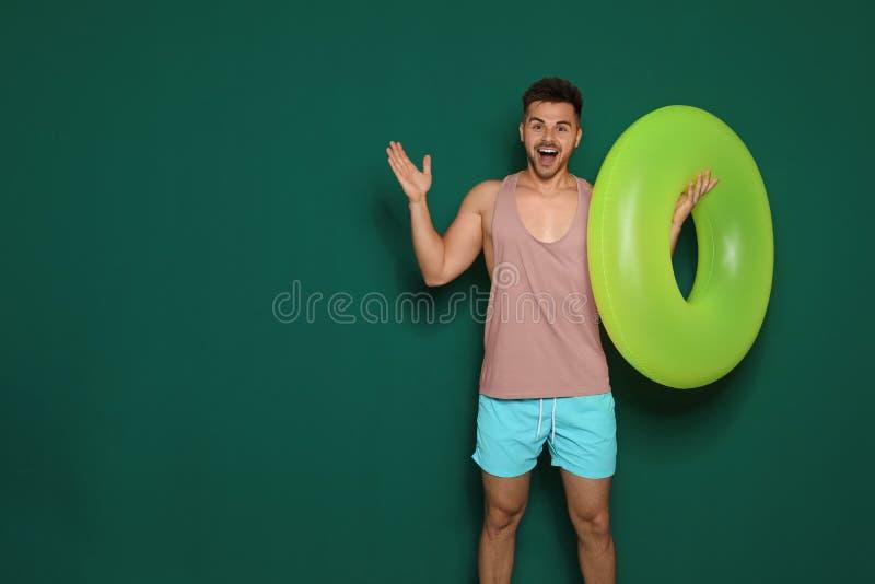 Grappige jonge mens met heldere ring op donkergroene achtergrond, ruimte voor tekst stock afbeeldingen