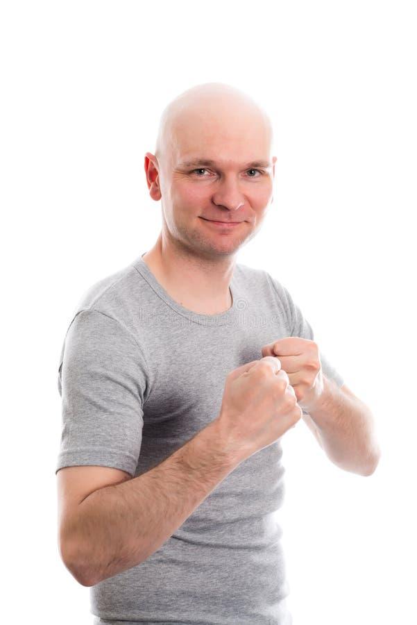 Grappige jonge mens met kale hoofd en vuisthanden stock afbeelding