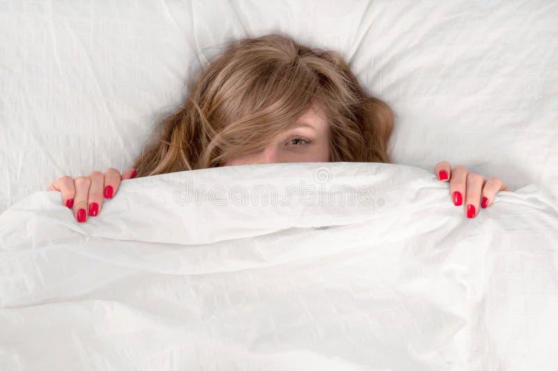 Grappige jonge mooie vrouw die in bed onder deken liggen royalty-vrije stock foto