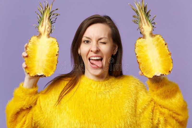 Grappige jonge vrouw in bontsweater die tongholding halfs van vers rijp ananasfruit tonen die op violette pastelkleur wordt geïso royalty-vrije stock afbeelding