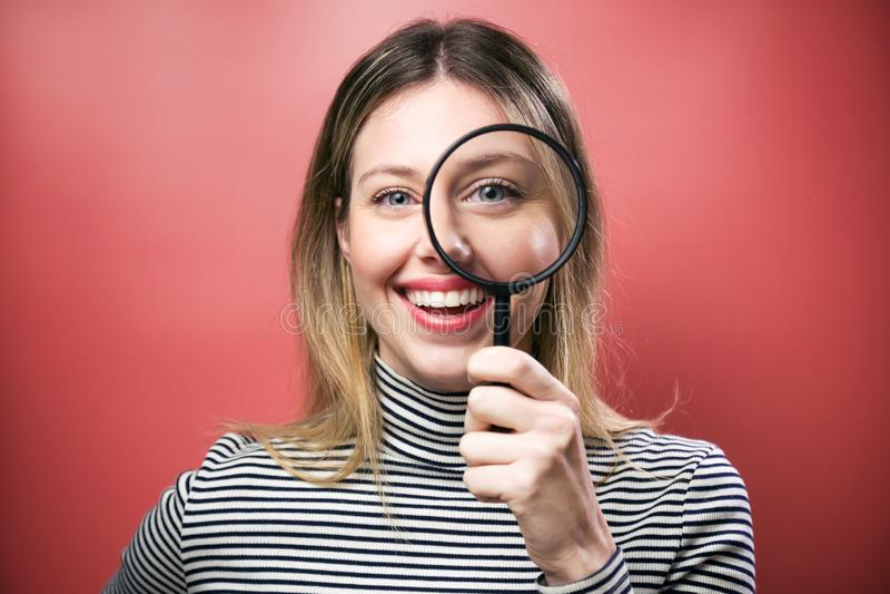 Grappige jonge vrouw die door vergrootglas de camera over roze achtergrond bekijken stock afbeeldingen