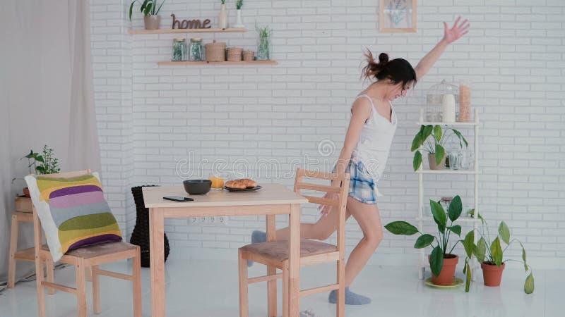 Grappige jonge vrouw die in keuken dansen die pyjama's in de ochtend dragen Het donkerbruine meisje in vrolijke stemming luistert stock afbeelding
