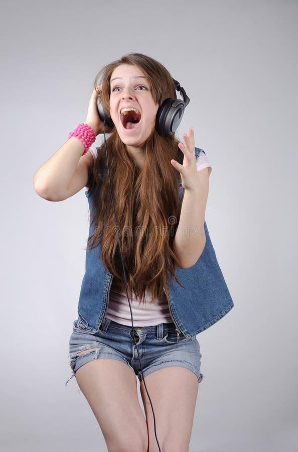Grappige jonge vrouw in het jeanswear luisteren aan muziek royalty-vrije stock afbeelding