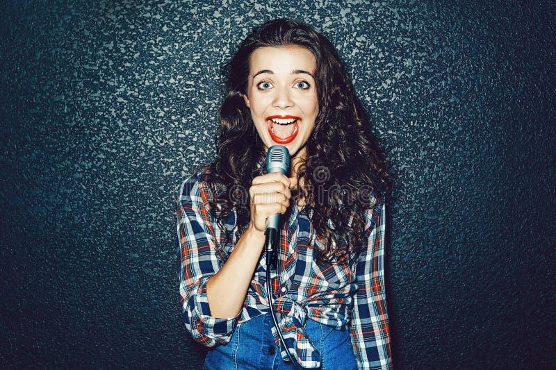 Grappige jonge vrouw met microfoon die iets zingen stock afbeeldingen