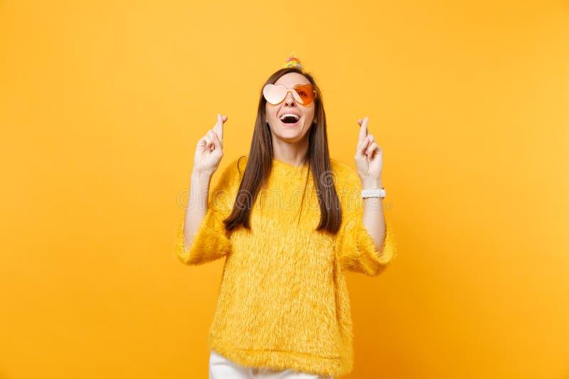 Grappige jonge vrouw in oranje hartglazen, de hoed die van de verjaardagspartij omhoog wachtend op speciaal ogenblik, die vingers royalty-vrije stock afbeeldingen
