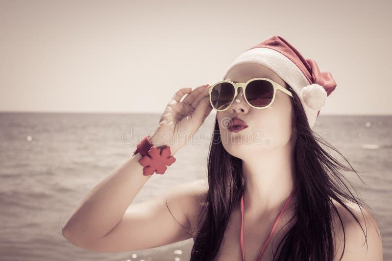 Grappige jonge vrouw in Santa Claus-hoed en zonnebril op een strand royalty-vrije stock foto