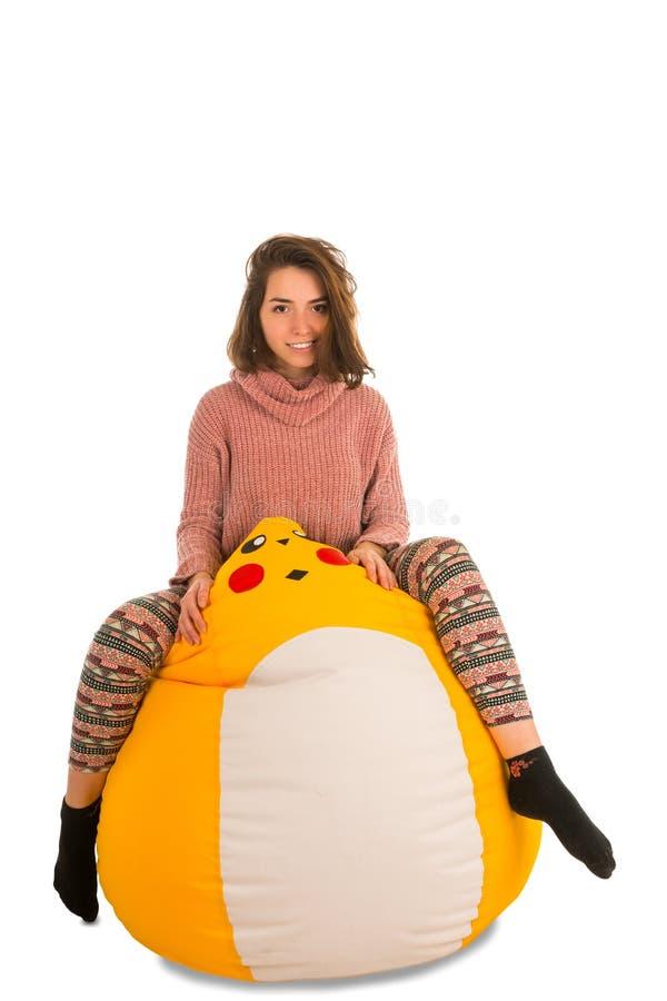 Grappige jonge vrouwenzitting op gele die beanbagstoel op wh wordt geïsoleerd stock afbeelding