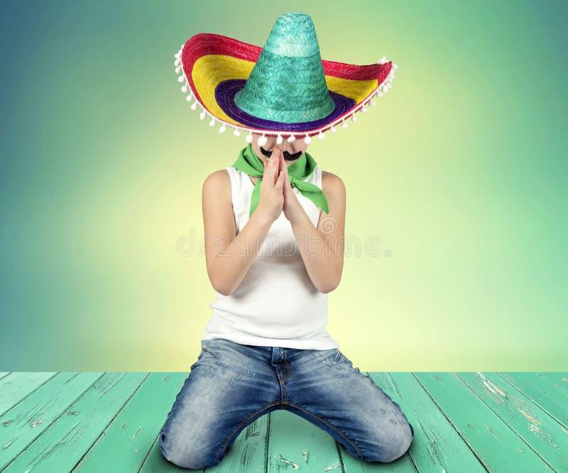 Grappige jongen met een valse snor en in Mexicaanse sombrero stock foto