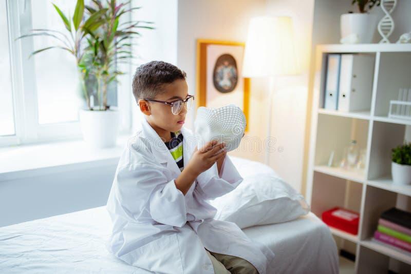 Grappige jongen wit jasje dragen en glazen die in het ziekenhuis spelen royalty-vrije stock foto
