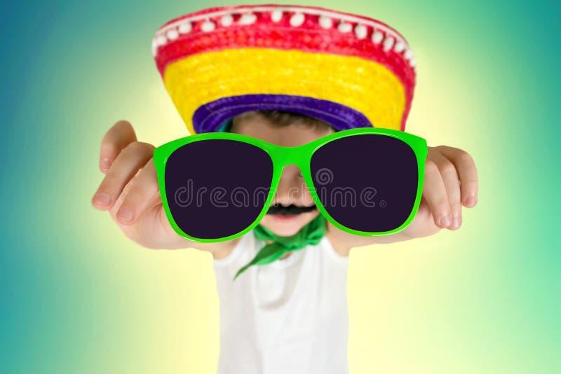 Grappige jongen in zonnebril en in Mexicaanse sombrero stock foto