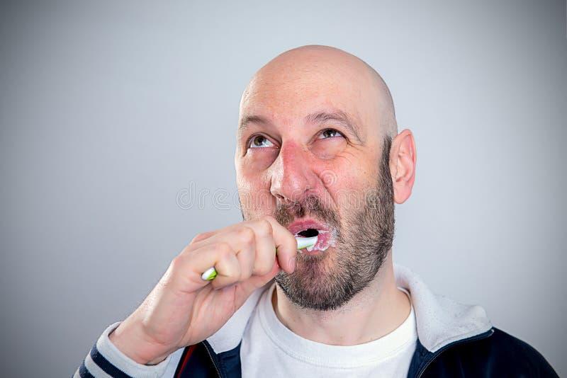 Grappige kale geleide mens het borstelen tanden royalty-vrije stock afbeeldingen