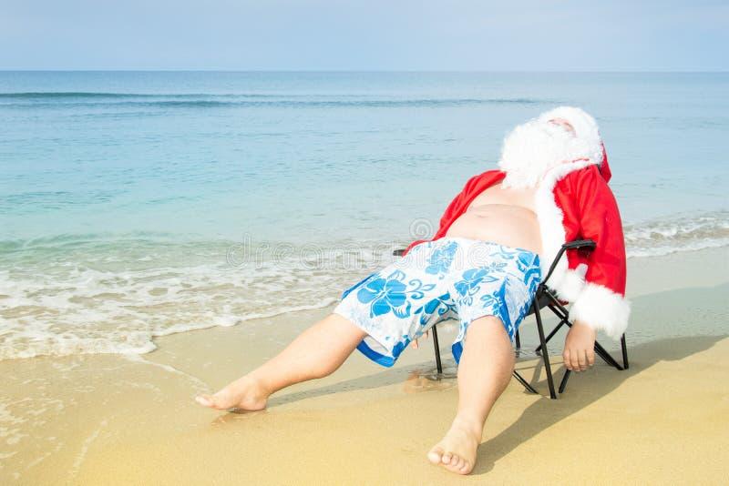 Grappige Kerstman in borrels op het strand Kerstmis in de keerkringen royalty-vrije stock afbeelding